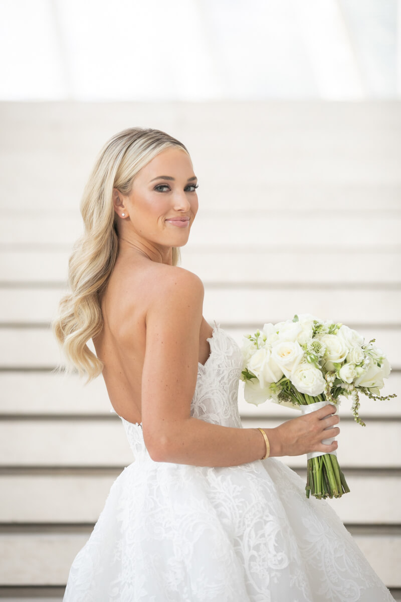 emily in monique lhuillier gown, smiling with flowers in hand