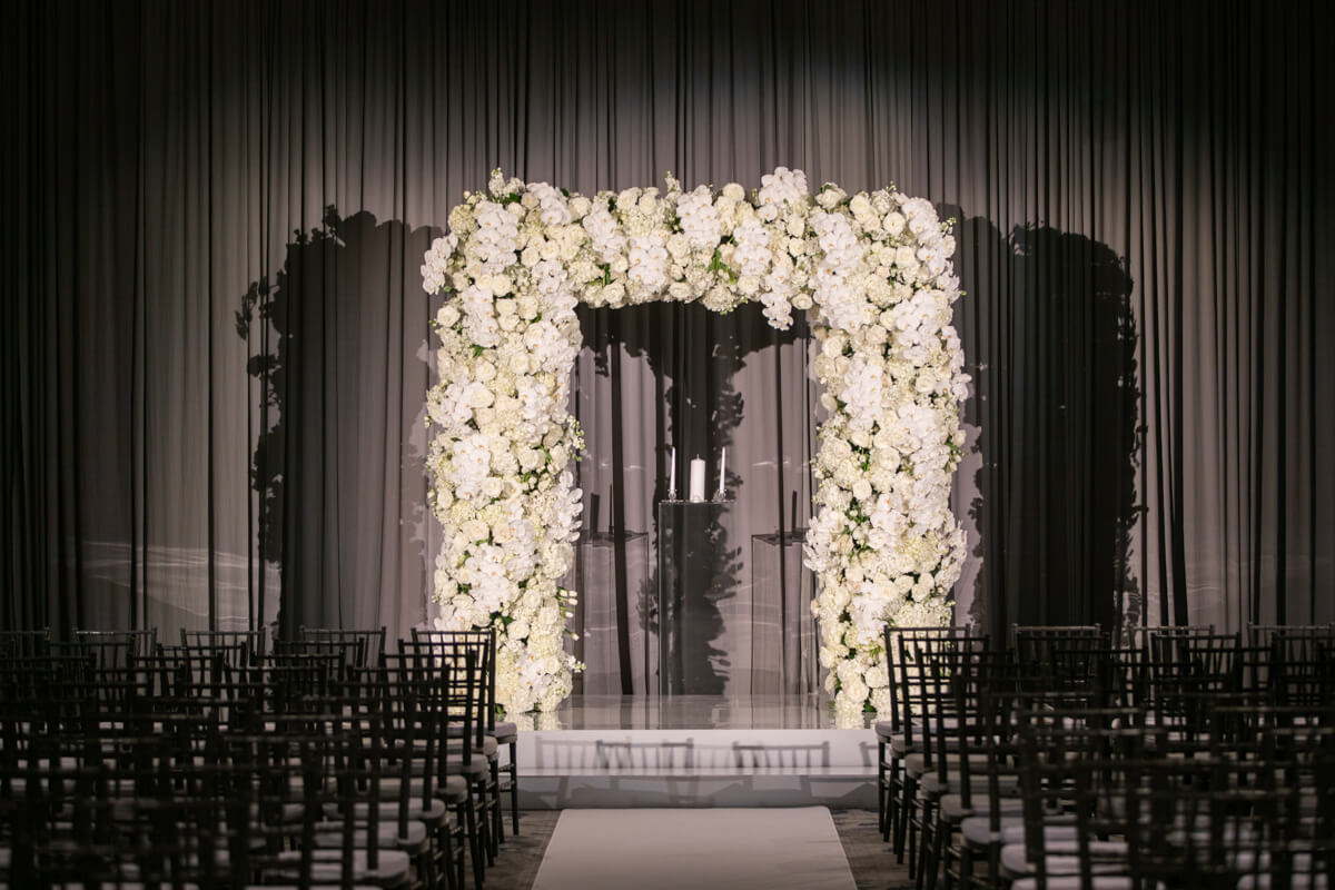 white floral arch in front of silver draping
