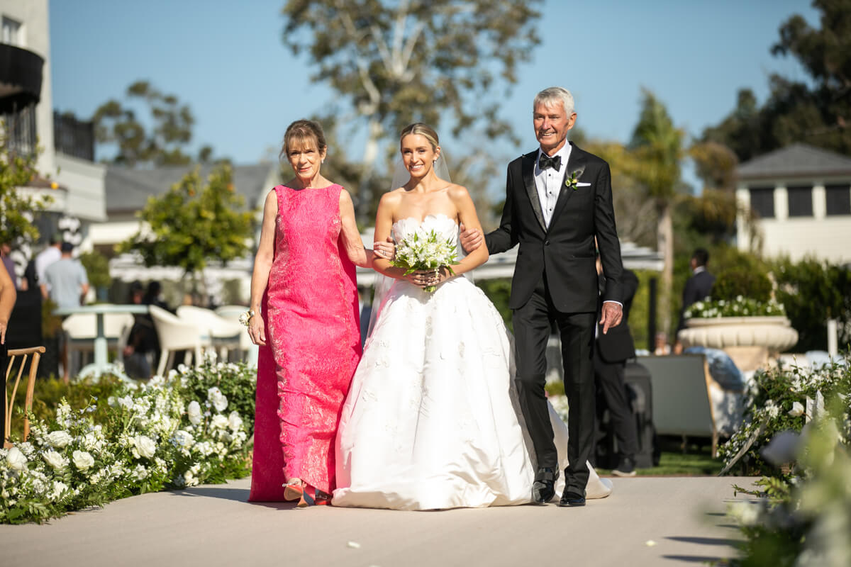 caitlin's mom and dad walking her down the aisle
