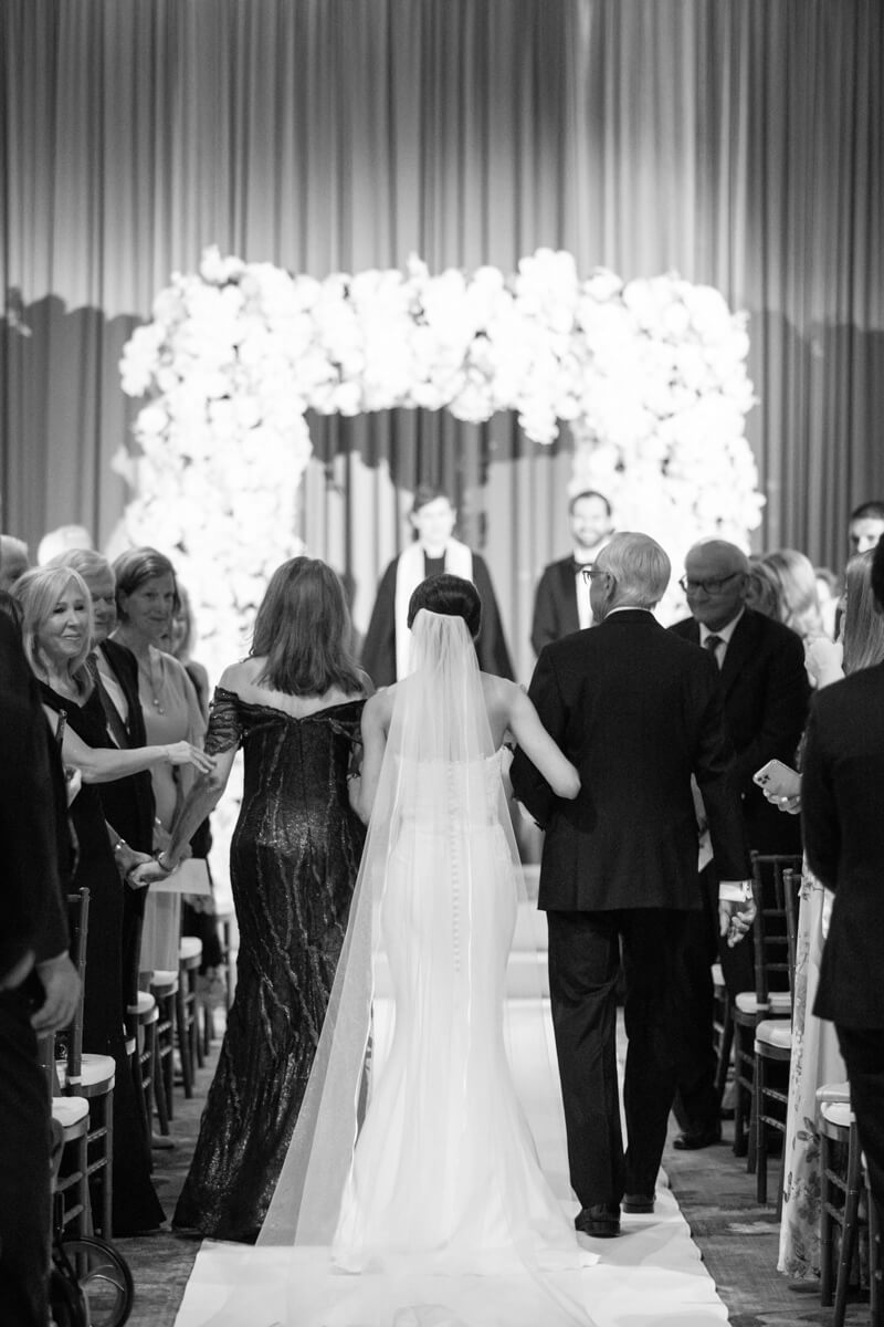 carey's mom and dad walking her down the aisle