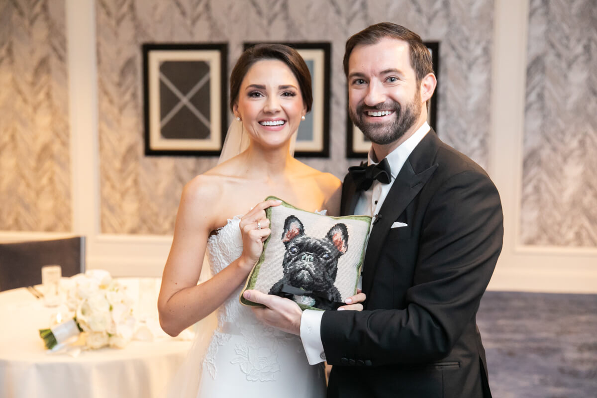 carey and david holding a pillow with a dog on it