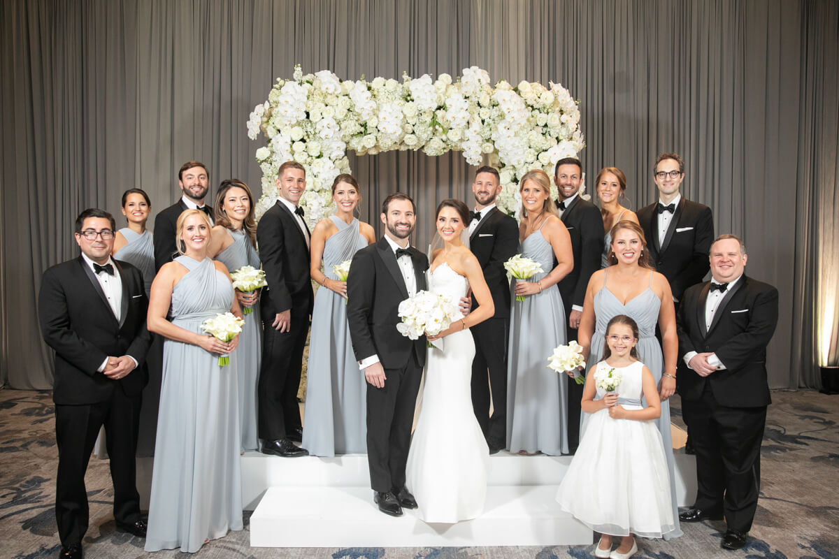 carey and david indoors with entire wedding party