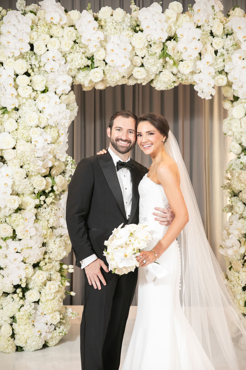 carey and david in front of white floral arch