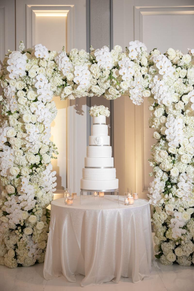 white wedding cake under white floral arch