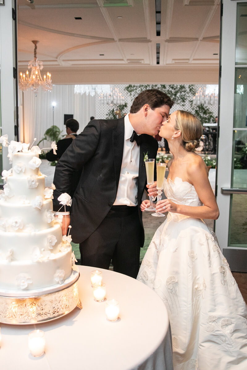 caitlin and geoffrey kissing behind their cake