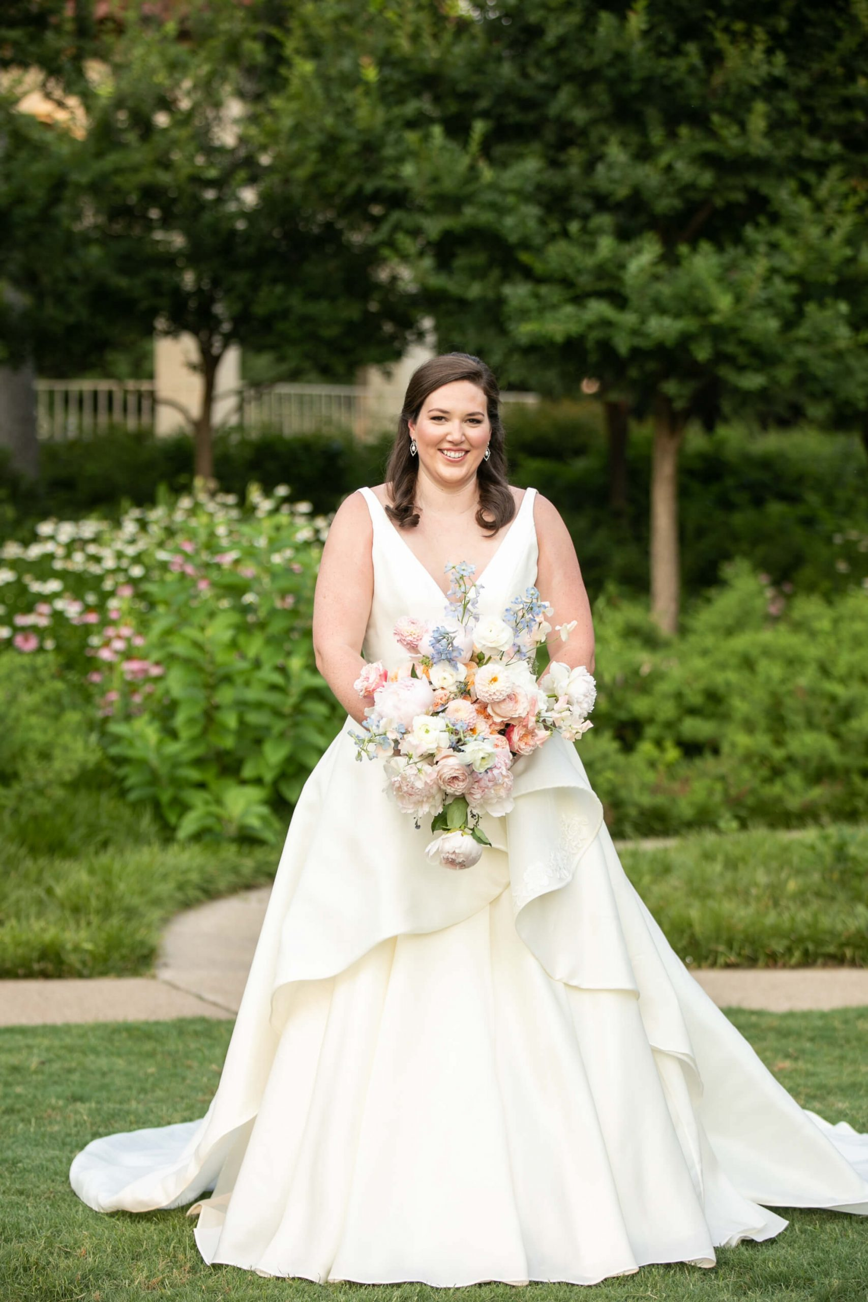 Carole Anne in her bridal gown in a park with bouquet